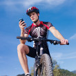 Young man with telephone riding mountain bike - Stock Photo