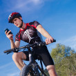 Stock Photo: Young man with telephone riding mountain bike