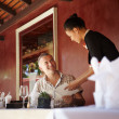 Asian waitress talking with client in restaurant - Foto Stock