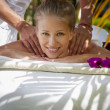Happy young woman smiling during massage in spa - Stock Photo