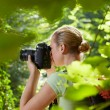 Young female photographer hiking in forest — Stock Photo #9758049