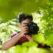 Young male photographer hiking in forest - Foto Stock