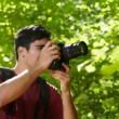 Young male photographer hiking in forest - Stock Photo