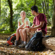 Couple sitting on trunk and eating snack after trekking - Foto Stock