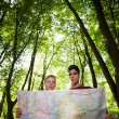 Stock Photo: Young couple looking at map during trek