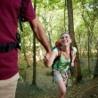 Young couple trekking in forest and holding hands — Stock Photo #9758377