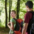 Couple with backpack doing trekking in wood — Stock Photo