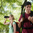 Young man and woman hiking in forest with binoculars - Stock Photo