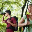 Young man and woman hiking in forest with binoculars — Stock Photo #9758448