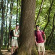 Environmental conservation: young hikers leaning on tree — Stock Photo