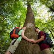 Environmental conservation: young hikers embracing large tree - 图库照片