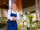 Joven bonita a mujer trabajo como florista en tienda y sonriendo — Foto de Stock