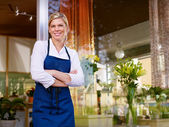 Young pretty woman working as florist in shop and smiling — Stok fotoğraf