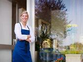 Genç kadın çiçekçi dükkanı olarak çalışan ve gülümseyen güzel — Stok fotoğraf