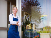 Young pretty woman working as florist in shop and smiling — Stock Photo