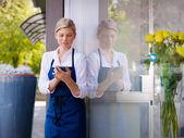 çiçekçi dükkanı ve kısa mesaj olarak çalışan genç kadın — Stok fotoğraf