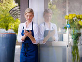 Young woman working as florist in shop and text messaging — Stock Photo