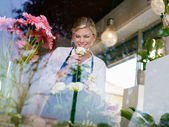 Blonde girl working in flowers shop with roses and gerbera — Stock Photo
