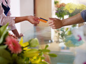 Client with credit card shopping in flowers shop — Stock Photo