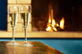 Two flutes filled with champagne near fireplace — Stock Photo