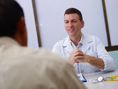 Doctor working and talking to old sick man in clinic — Stock Photo