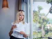 Business woman drinking and staring out of window — Stock Photo