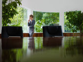 Businesswoman contemplating out of window in meeting room — Stockfoto