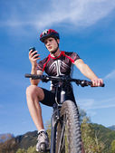 Young man with telephone riding mountain bike — Stock Photo
