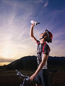 Portrait of man training on mountain bike at sunset — Stock Photo