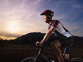 Young man training on mountain bike at sunset — Stock Photo