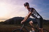 Portrait of man training on mountain bike at sunset — Stock Photo