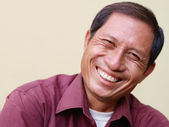 Happy mature Asian man smiling and looking at camera — Photo