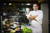Asian chef smiling at camera in restaurant kitchen — Stockfoto
