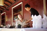 亚洲女服务员交谈中餐厅的客户端 — 图库照片