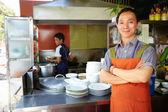 Hombre que trabajaba como cocinero en cocina de restaurante asiático — Foto de Stock