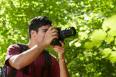Young male photographer hiking in forest — Zdjęcie stockowe
