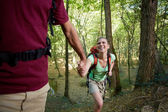 Young couple trekking in forest and holding hands — Stok fotoğraf