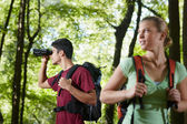 Young man and woman hiking in forest with binoculars — Zdjęcie stockowe