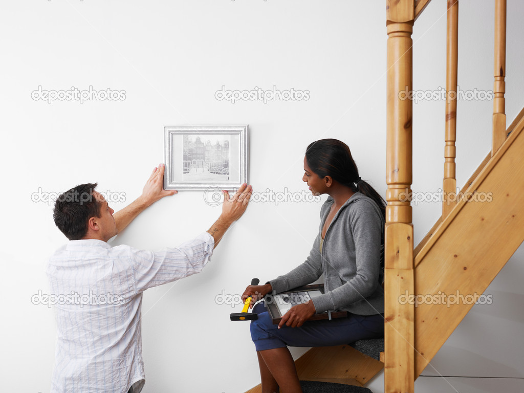 Mid adult multiethnic couple hanging pictures to the wall and smiling. Horizontal shape, copy space — Stock Photo #9750969