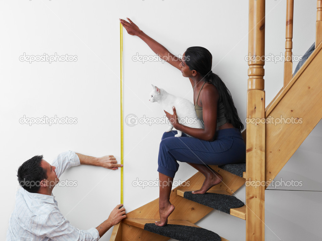 Do it yourself: couple measuring wall to hang picture at home. Horizontal shape, copy space — Stock Photo #9751014