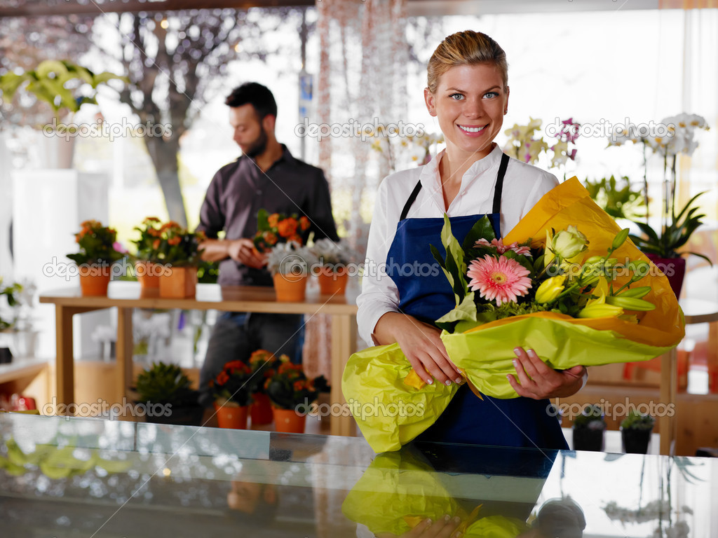 Female sales assistant working as florist and holding bouquet with customer in background. Horizontal shape, waist up — Photo #9751762
