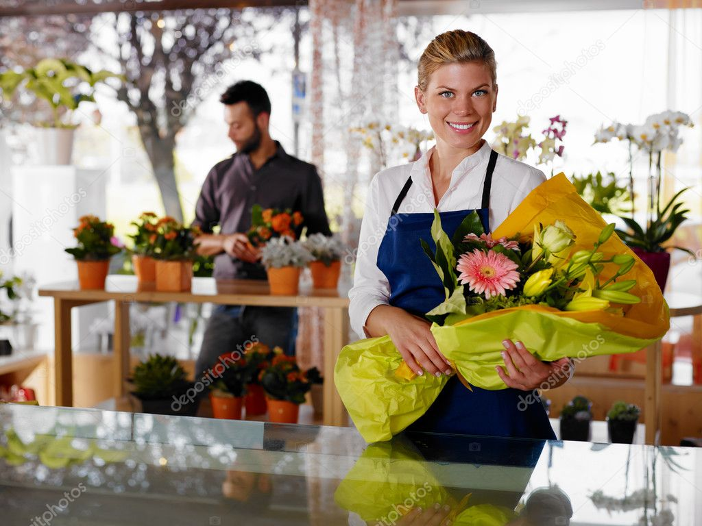 Female sales assistant working as florist and holding bouquet with customer in background. Horizontal shape, waist up — Foto Stock #9751762