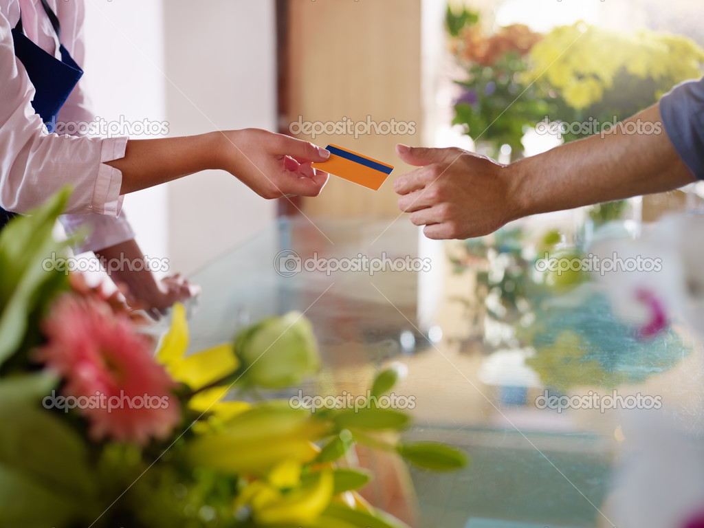 Young woman working as florist giving credit card to customer after purchase. Horizontal shape, closeup  Stock Photo #9751799