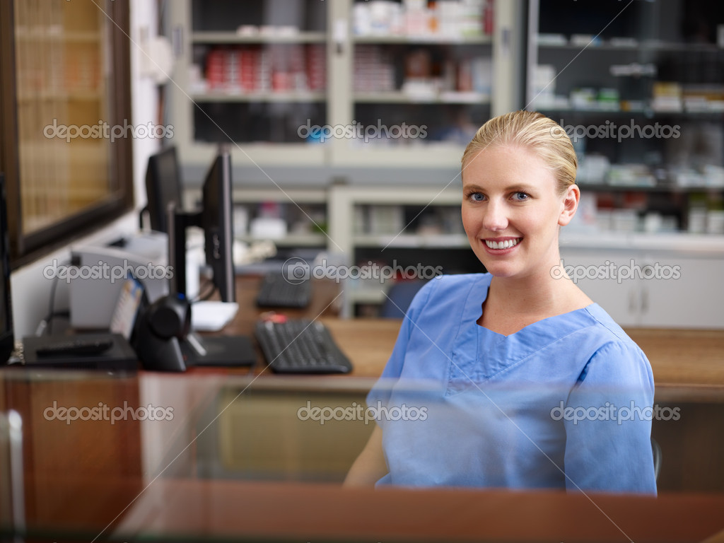 Young woman at work as receptionist and nurse in hospital, looking at camera — Stock Photo #9752094
