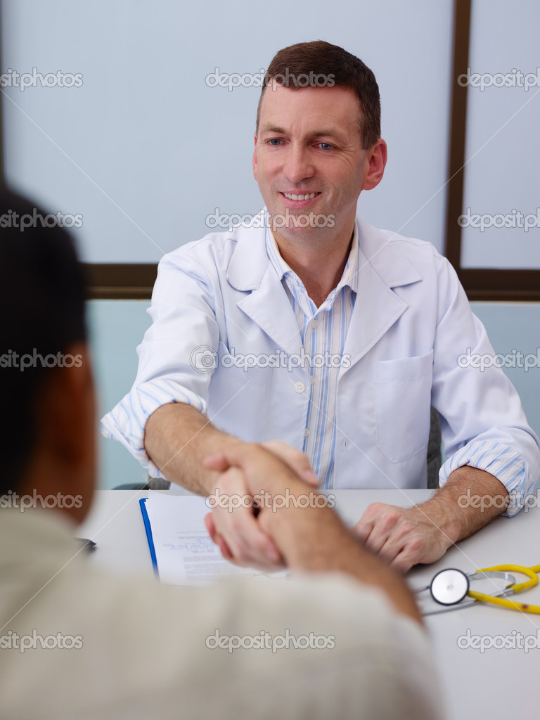 Friendly doctor working and handshaking old male patient in hospital office. Focus on background — Stock Photo #9752937