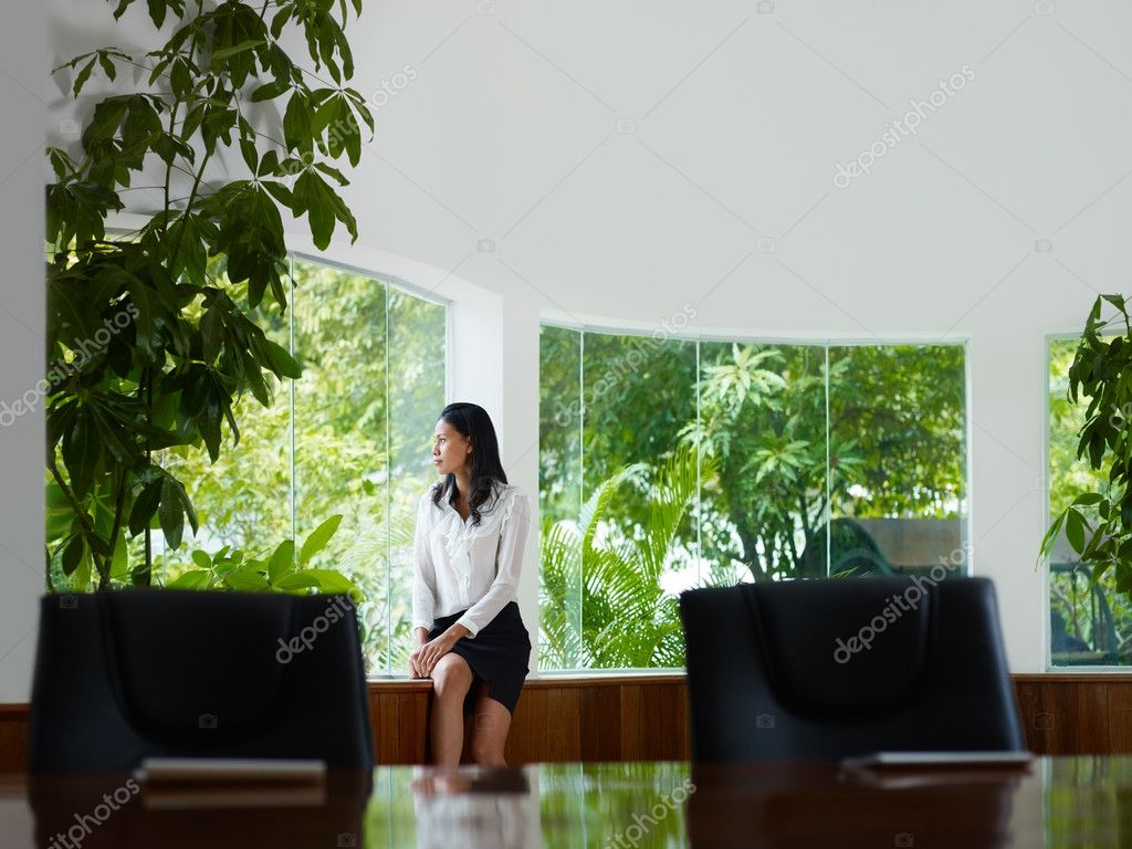 Beautiful Asian female manager looking out of the window in office. Front view, copy space — Stock Photo #9754750