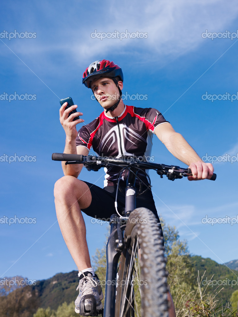 Sports activity: young adult cyclist riding mountain bike and text messaging on cellphone. Vertical shape, low angle view — Stock Photo #9755550