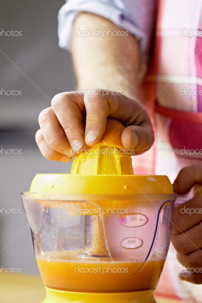 Closeup of man using citrus-fruit squeezer, preparing orange juice. Vertical shape, cropped view  Stock Photo #9756315
