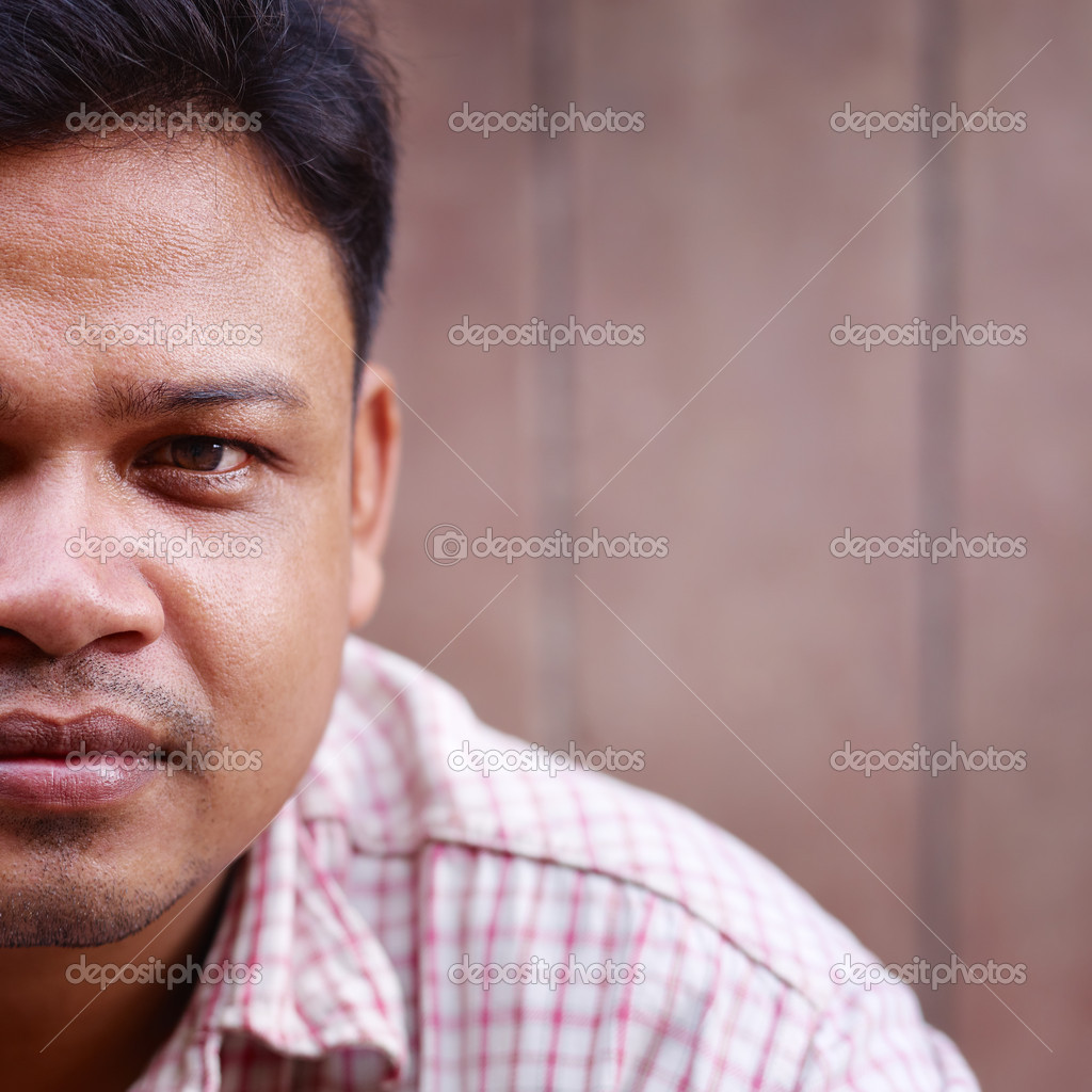Portrait of asian 30 years old man looking at camera against brown wall.