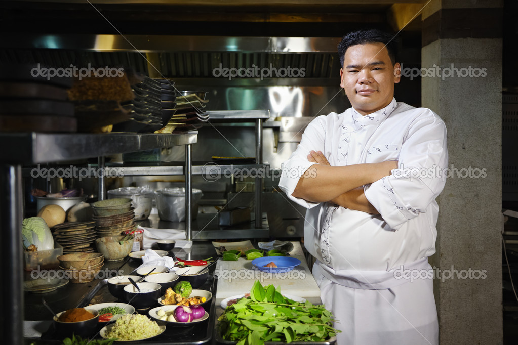 Portrait of adult man at work as chef in the kitchen of an Asian restaurant, posing with arms crossed — Stock Photo #9757199
